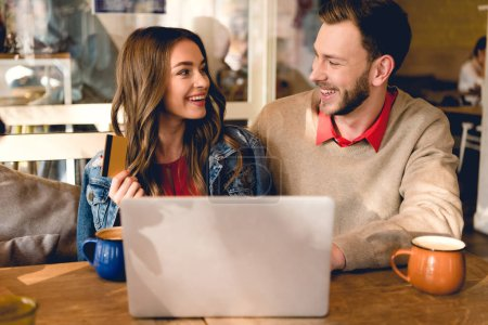happy young woman holding credit card and looking at cheerful man near laptop