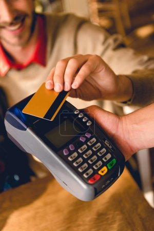 Photo for Cropped view of cheerful man holding credit card while paying in cafe - Royalty Free Image