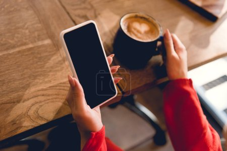 Photo for Cropped view of woman holding smartphone with blank screen near cup of coffee - Royalty Free Image