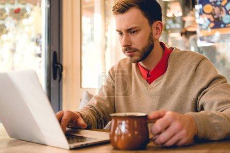 Photo pour Blogueur concentré regardant ordinateur portable tout en tenant une tasse de café - image libre de droit