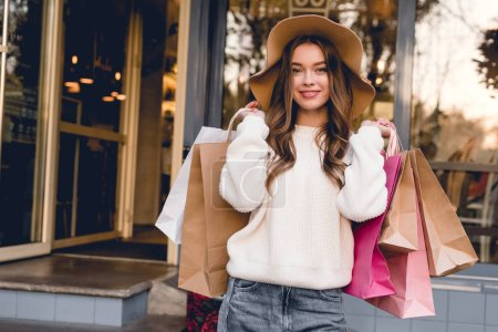 Photo for Happy girl in hat smiling while holding shopping bags - Royalty Free Image