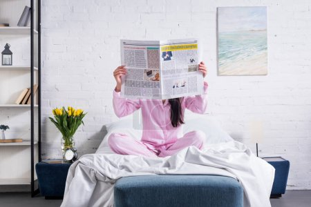 obscured view of woman in pajamas with newspaper in bed at home
