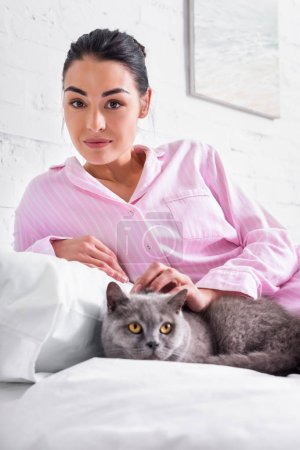 Photo pour Portrait de femme avec la Grande-Bretagne shorthair chat reposant sur le lit à la maison - image libre de droit