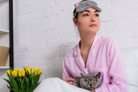 pensive woman in pajamas and sleeping mask with britain shorthair cat resting in bed at home
