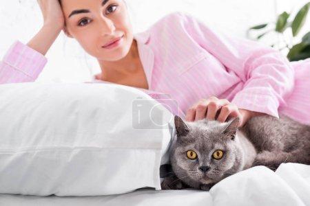 Photo pour Portrait de jolie femme en pyjama avec chat shorthair de Grande-Bretagne reposant sur le lit à la maison - image libre de droit