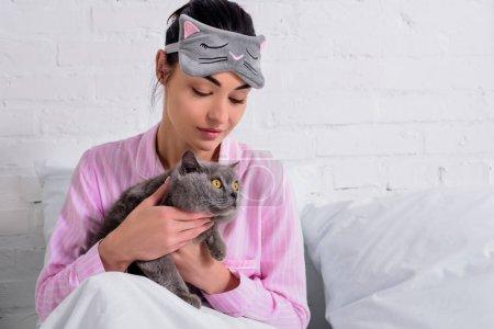 Photo pour Portrait de femme en pyjama et masque de sommeil avec chat shorthair de Grande-Bretagne au repos au lit à la maison - image libre de droit