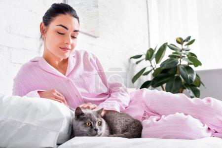 Photo pour Femme souriante, caresser le chat shorthair Grande-Bretagne en position couchée sur le lit à la maison - image libre de droit