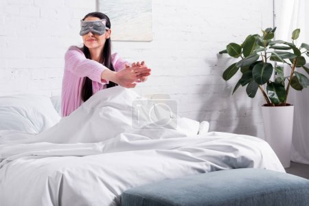 woman in pink pajamas and sleeping mask stretching in bed in morning