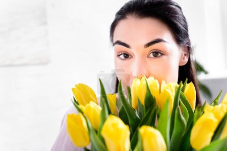 partial view of woman with bouquet of yellow tulips looking at camera at home