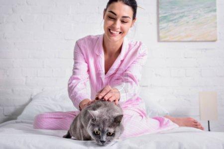 Photo pour Femme heureuse avec chat shorthair de Grande-Bretagne reposant sur le lit à la maison - image libre de droit