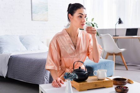 attractive woman in silk bathrobe making tea while having tea ceremony in morning at home