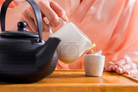 partial view of woman pouring tea into cup while having tea ceremony at home