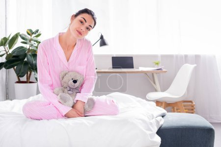 attractive woman in pink pajamas with teddy bear sitting on bed at home