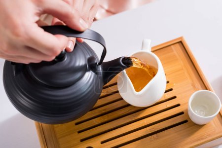 partial view of woman pouring tea into jug while having tea ceremony at home