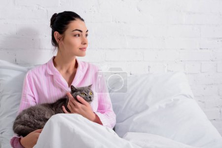 portrait of pensive woman with britain shorthair cat looking away while resting on bed at home