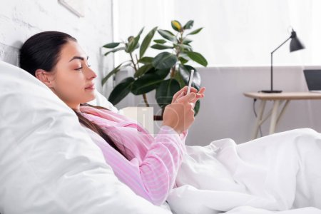 side view of attractive woman in pajamas using smartphone while resting in bed at home
