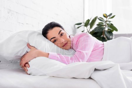 portrait of woman in pink pajamas resting in bed in morning at home