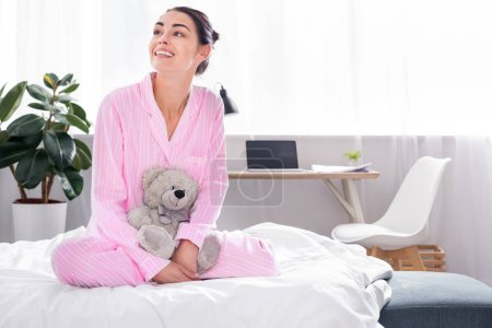 cheerful woman in pink pajamas with teddy bear sitting on bed at home