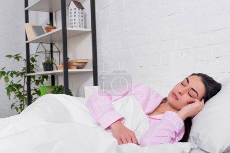 Photo pour Portrait de femme en pyjama rose dormant au lit à la maison - image libre de droit