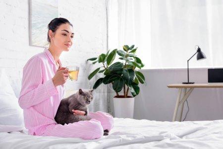 Photo pour Vue de côté de femme avec une tasse de thé et la Grande-Bretagne chat shorthair reposant sur le lit à la maison - image libre de droit