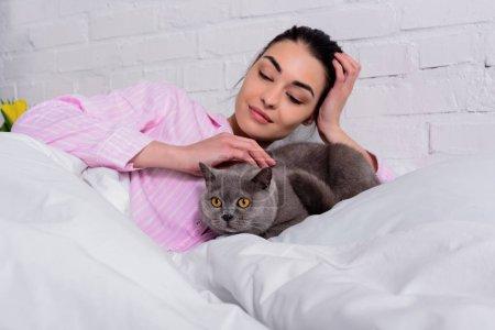 Photo pour Portrait de femme souriante en pyjama caresser le chat shorthair Grande-Bretagne tout en reposant sur le lit à la maison - image libre de droit