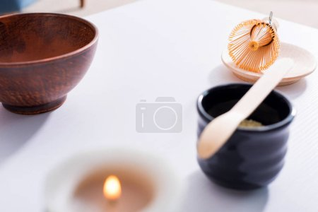close up view of arranged ceramic cutlery for tea ceremony on white tabletop