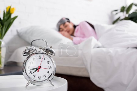 selective focus of clock and woman in pink pajamas and sleeping mask sleeping in bed at home