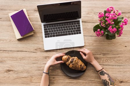 cropped shot of woman at workplace with laptop, books and croissant on plate