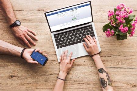 plan recadré de l'homme avec smartphone avec logo facebook à la main et la femme à la table avec ordinateur portable facebook site Web et fleur de kalanchoe