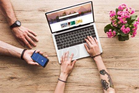 Photo pour Plan recadré de l'homme avec smartphone avec logo facebook à la main et la femme à la table avec ordinateur portable avec site Web shutterstock et fleur de kalanchoe - image libre de droit