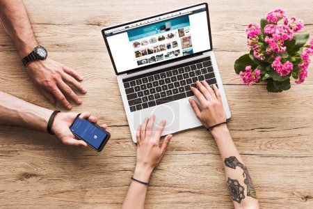 Photo for Cropped shot of man with smartphone with facebook logo in hand and woman at tabletop with laptop with amazon website and kalanchoe flower - Royalty Free Image