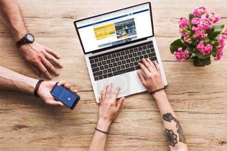 plan recadré de l'homme avec smartphone avec logo facebook à la main et la femme à la table avec ordinateur portable avec site bookingcom et fleur de kalanchoe