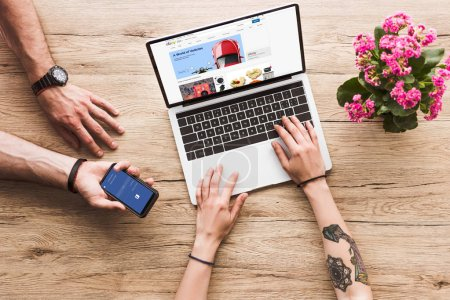 cropped shot of man with smartphone with facebook logo in hand and woman at tabletop with laptop with ebay website and kalanchoe flower