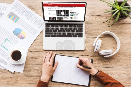 Photo for Partial view of man making notes in notebook at workplace with laptop with bbc website, papers, cup of coffee and headphones - Royalty Free Image
