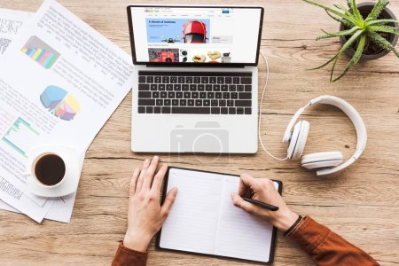 cropped image of man working at table with laptop with ebay logo, headphones, textbook, pen, infographics, coffee cup and potted plant