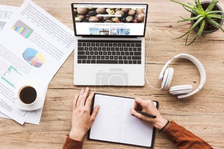 partial view of man working at laptop with depositphotos website, headphones, textbook, pen, infographics, coffee cup and potted plant at table