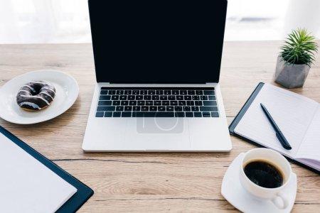 Photo pour Gros plan de l'ordinateur portable avec écran blanc, presse-papiers vide et manuel, plante en pot, beignet et tasse à café - image libre de droit