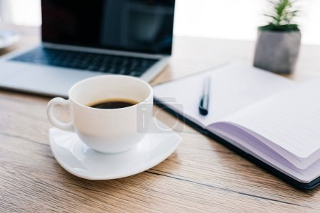close up view of coffee cup, empty textbook and laptop with blank screen on wooden table
