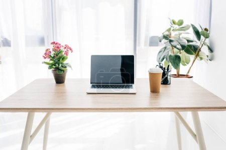 front view of laptop with blank screen, coffee cup, flowers and stationery on table