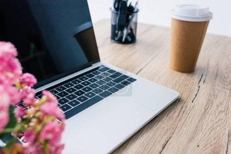 Photo pour Vue d'ordinateur portable avec écran blanc, fleurs, tasse de café et de papeterie en papier sur la table - image libre de droit