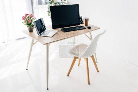 Photo pour Intérieur du lieu de travail avec chaise, fleurs, café, papeterie, ordinateur portable et ordinateur sur table en bois - image libre de droit