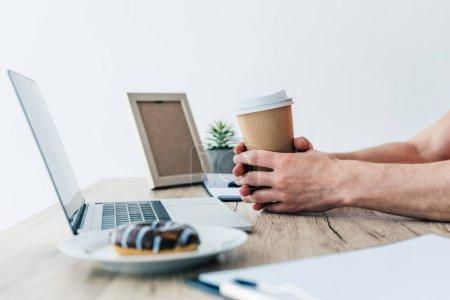 Photo pour Homme tenant la tasse de café à table avec ordinateur portable, manuel, presse-papiers, cadre photo, plante en pot et en anneau sur plaque - image libre de droit