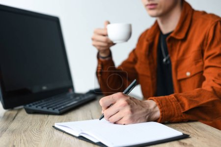Photo for Partial view of man drinking coffee and writing in textbook at table with computer and computer keyboard - Royalty Free Image