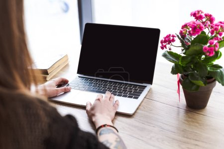 cropped image of woman with tattooed hand typing on laptop at table with flowers and books