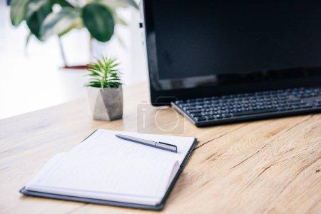 Photo pour Image rapprochée d'un manuel vide, d'un stylo, d'une plante en pot, d'un clavier d'ordinateur et d'un clavier d'ordinateur à la table - image libre de droit
