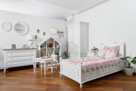 Interieur eines modernen hellen Schlafzimmers mit schmalem Bett und weißen Möbeln