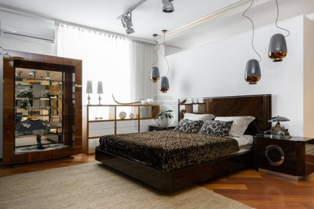 interior of modern light bedroom with lamps, shelves and brown bedsheets