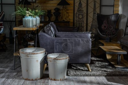 interior of modern retro styled living room with grey armchair and trash cans