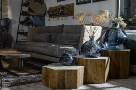 Photo for Interior of modern retro styled living room with grey sofa and vases on wooden shelves - Royalty Free Image