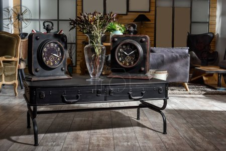 Photo for Interior of modern retro styled living room with two clocks and dried flowers on wooden black table - Royalty Free Image